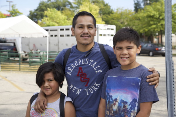Everardo Valadez stands with his daughter and son at the Back to School Fair at Bishop Plaza. (The Gate/Gloria Talamantes)
